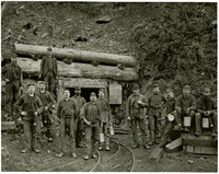 Thirteen miners stand in front of the entrance to Blue Canyon Mine