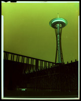 View from below of Seattle Space Needle with white Seattle Center buildings in foreground