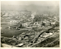 Aerial view of pulp mill , possibly Puget Sound Pulp and Timber, on shore of Bellingham Bay with city of Bellingham beyond