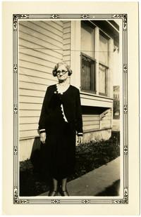Woman poses on sidewalk outside residence