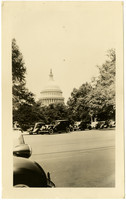Dome of U.S. Capitol building seen through trees and across street full of cars