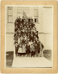 Large group of school children pose on steps of school with American flag at top of steps