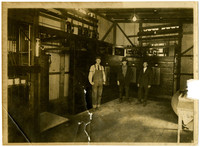 Three young men stand in a room, possibly an electrical control room of a factory