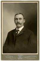 Studio portrait of unidentified man in suit with moustache