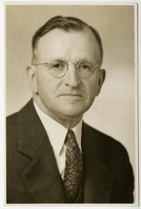 Studio portrait of R.G. Wright in spectacles with suit and tie