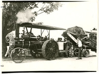 Several men tend to equipment that is hitched to tractor, possibly as part of a parade