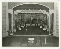 View from balcony of stage with actors or dancers performing, organist below stage.