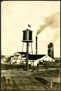 A British ensign flies atop a water tower adjacent to a mill or cannery