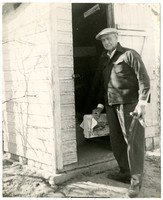 Unidentified man stands in front of an open door to a wooden structure