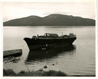 An unidentified ship tied up at a low dock with a mountain in the background, possibly Lummi Island