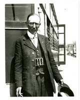 Streetcar conductor, possibly Harry Loft, in uniform with change maker, standing next to trolley
