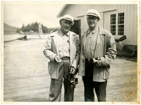 Two unidentified men, each holding a movie camera.