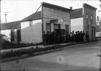 Unidentified men, women and children dressed in their good clothes standing in line outside of a photograph studio