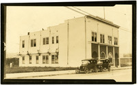 Exterior street view of Labor Temple (union building) on State Street, Bellingham, WA, with two early-model cars parked in front