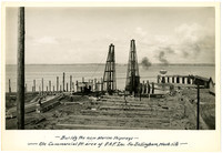 View of construction scene at water's edge of Bellingham Bay with piles of wood beams and two pile drivers