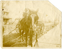 A little girl sitting on a horse with an unattached wagon behind it and a house across a muddy street in background