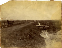 Man in horse-drawn buggy travels down dirt road next to irrigation ditch, surrounded by corrals and farmland
