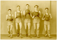 Five members of a basketball team pose while holding balls