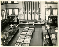 View from above of room full of display cases in a museum or exhibition hall, with a model-sized five-masted schooner along far wall