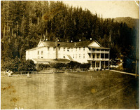 Large lawn in front of grand hotel set in forested hillside
