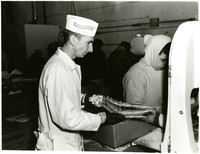 Man in labcoat and cap holds legs of snow crab while waiting for worker to use bandsaw to cut crab for packaging