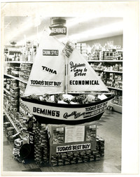 Grocery store promotional display of Deming's Tuna with miniature sail boat and stacks of cans