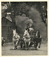 Three galloping draught horses hitched to steam-fired engine, rounds a city street corner with steam billowing