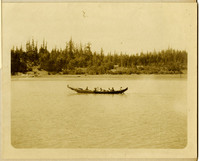 Native American canoe in the water with six people in it, forested shoreline in background