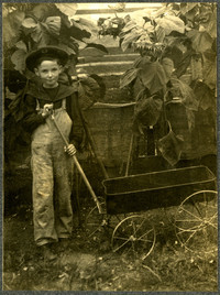 Young boy in wide-brimmed hat and overalls stands with toy wagon