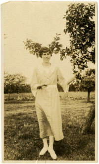 Young woman poses in orchard, holding a plum