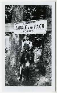 """Young boy in overalls rides a pack mule beneath sign for """"C.Bourn Saddle and Pack Horses"""""""