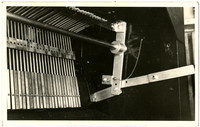 Postcard of a salmon-skinning machine with two rows of closely-spaced rods perpendicular to each other, with operating lever