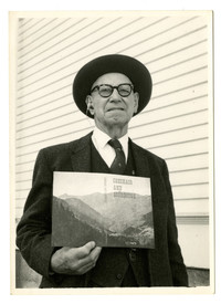 """Percival Jeffcott, in suit, holds his book titled """"Checaco and Sourdough"""""""