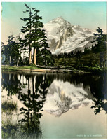 Hand tinted photo of snow-covered Mt. Baker in the background with a lake or tarn in the foreground