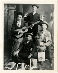 Four band members in suits sit for studio portrait with instruments and promotional material