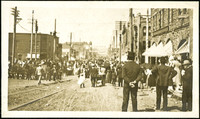 View looking up unpaved street with trolly tracks down center and crowds of people looking into distance