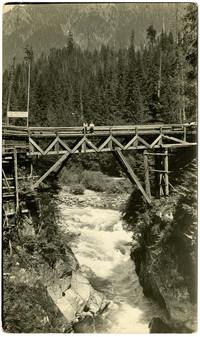 Wooden bridge over gorge with whitewater river