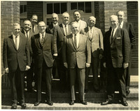 Eleven unidentified men wearing suits stand on steps of brick building