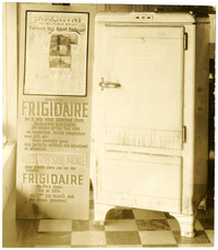 Icebox-refrigerator on display with promotional sign with Bellingham Herald newspaper headlining the Fairhaven School fire from which the refrigerator was removed