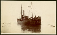 """The double-masted, single smokestack, fishing steamer  """"Kingfisher"""" with fourteen men standing on deck, some in workers' clothes, some in suits or uniforms"""