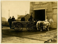 """Bellingham No. 2"" fire department hose wagon with two horses is parked in front of open doors of fire house with four men including the driver"