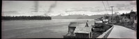 Probably a view of Petersburg, Alaska taken from a plank street at the water's edge with Frederick Sound in the distance and snow-capped mountains beyond