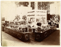 "Several sets of display cases, with ""Washington"" adorning the bases, are full of produce in a large exhibition hall"