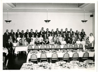 Unidentified social event of over fifty men and women standing and seated at a long table set for dinner