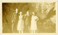 Two women and two men are posed under an rocky outcrop