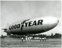 Goodyear Blimp rests on field at Bellingham Airport with onlookers in foreground