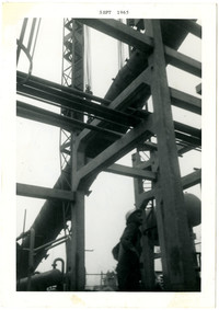 Man in hardhat stands beneath tall metal structure
