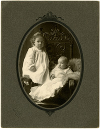 Portrait of two seated children in christening gowns