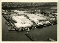 Aerial view of Bellingham industrial waterfront with cold-storage wharehouses, fuel tanks, moored vessels, part of a breakwater at bottom and neighborhoods above bluff at top