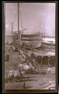 Shipyard with large ship under construction, with two teams of horses in the foreground